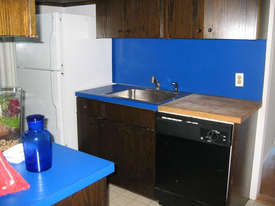 Dan and Leah Klein's kitchen in Cambridge with its dated cabinets and bright blue Formica counters.